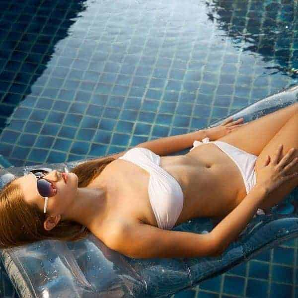 A woman on a floating mattress in a swimming pool