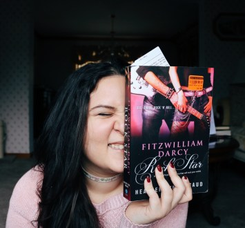 Me holding up a copy of Fitzwilliam Darcy, Rock Star and smiling