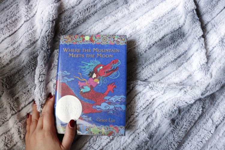 where the mountain meets the moon book on a grey and white blanket with my hand holding the book