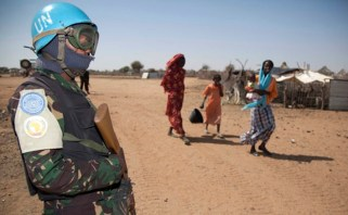 Women with children walk near a soldier of Darfur's joint U.N./African Union UNAMID peacekeeping force outside the UNAMID team site in Khor Abeche