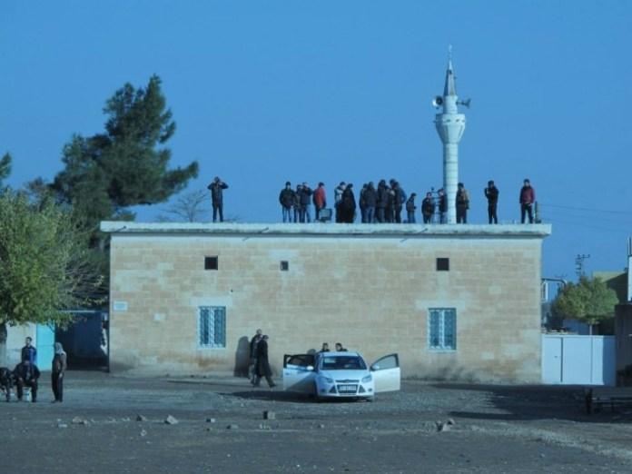 Abitanti di Mehser guardano i combattimenti dal tetto della moschea