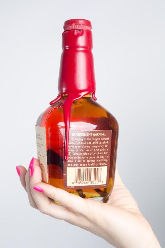 brittany holding homemade vanilla bean infused bourbon recipe