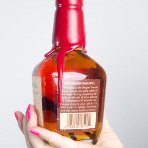 brittany holding homemade vanilla bean infused bourbon recipe