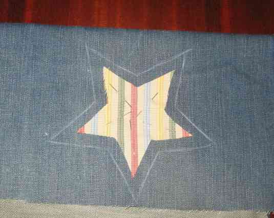 Sujetamos con alfileres la estrella de colores sobre la tela vaquera