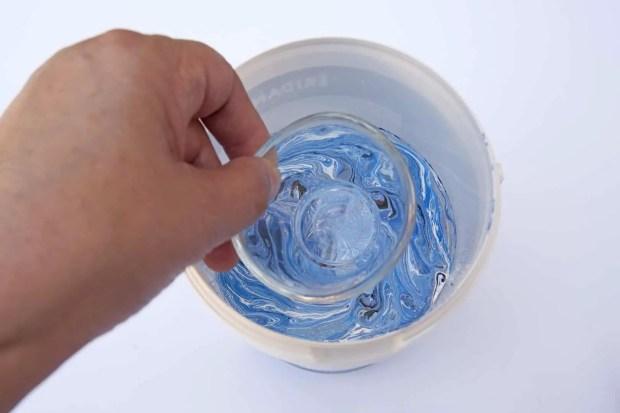Sumergiendo la pieza de cristal en el bote con las pinturas de uñas mezcladas