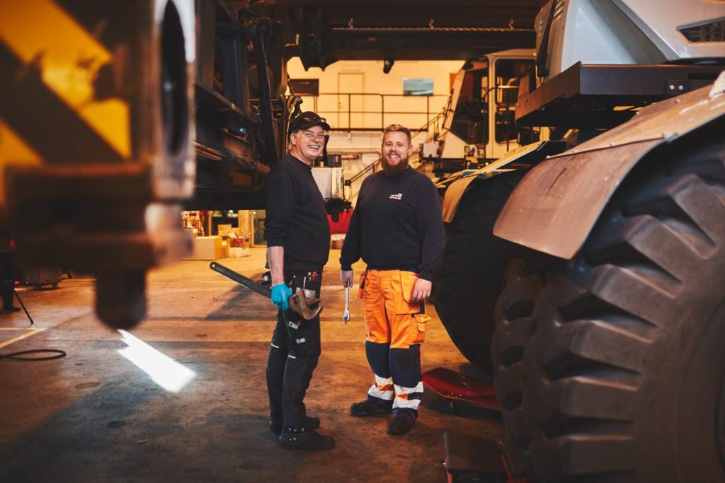 Två medarbetare från verkstaden står mitt emot varandra och ler mot betraktaren