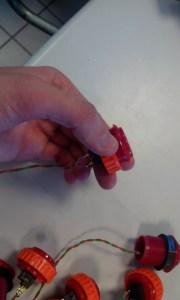 Voici à quoi ressembleront vos boutons une fois reliés à des fils. Torsadés bien les deux fils ensemble pour éviter que ceux ci s'emmêlent.