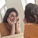 Mulher feliz se olhando no espelho.