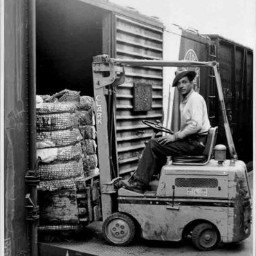 A worker moving goods with a forklift onto a train