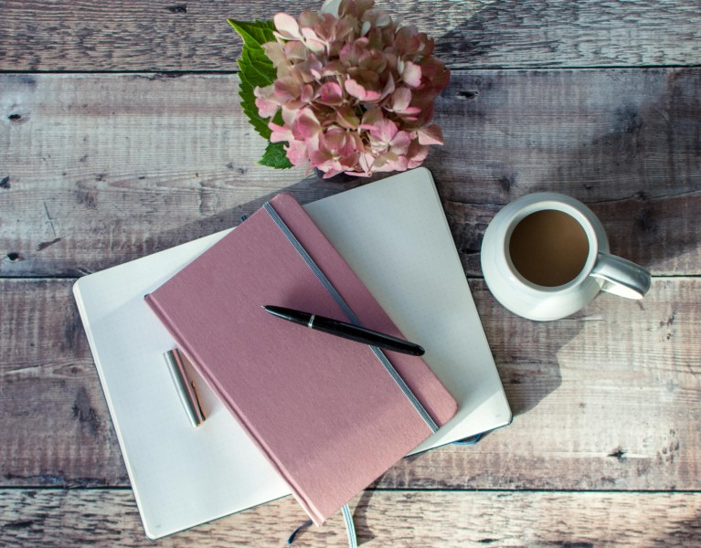 pink linen covered notebook and open journal with coffee cup