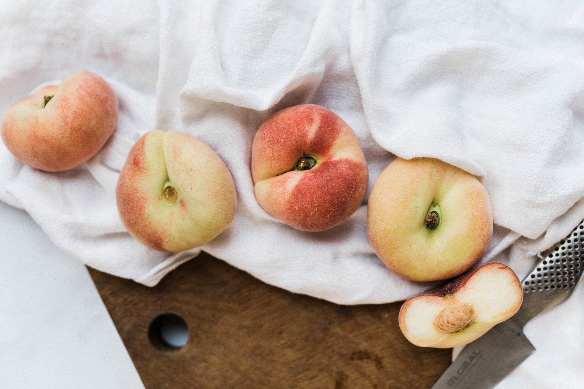 flat peaches on linen, food photography
