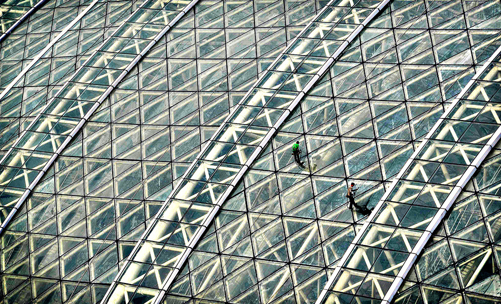"Workers clean the glass roof of the ""New...Workers clean the gla"