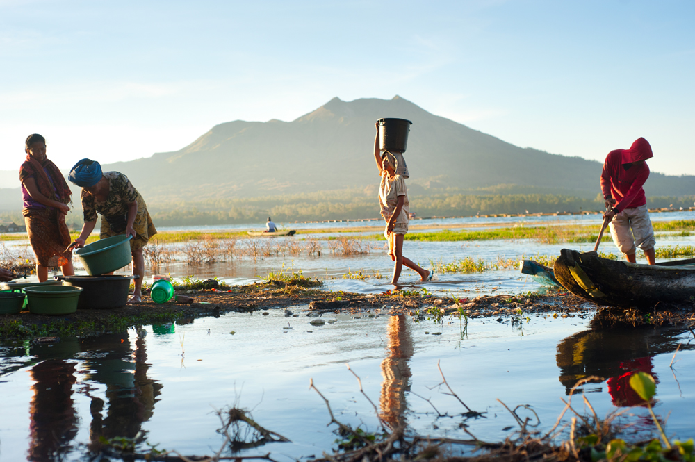 Balinese fishermen on a lake, Batur volcano in the background