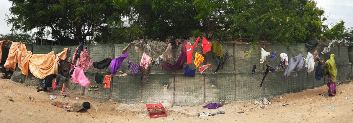 Mogadishu, SOMALIA 23.05.2014 A woman hangs her families clothes to dry on the perimeter of the AMISOM (African Union Mission in Somalia) base. Mogadishu, Somalia. Rick Findler / Story Picture Agency
