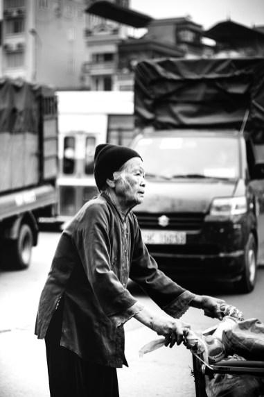 Elderly woman crossing the road in Hanoi.