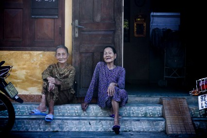Two elderly women chatting on the streets of Hội An