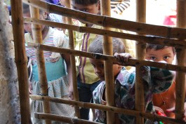 Curious family and friends peek through the grated bamboo door and threaten the attention of the child being tested.