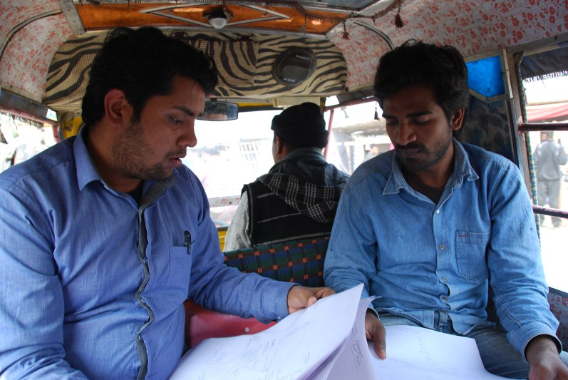 Research assistants, Nilotam and Ranjeet, look over hand-drawn maps in the back of this CNG to find villages.