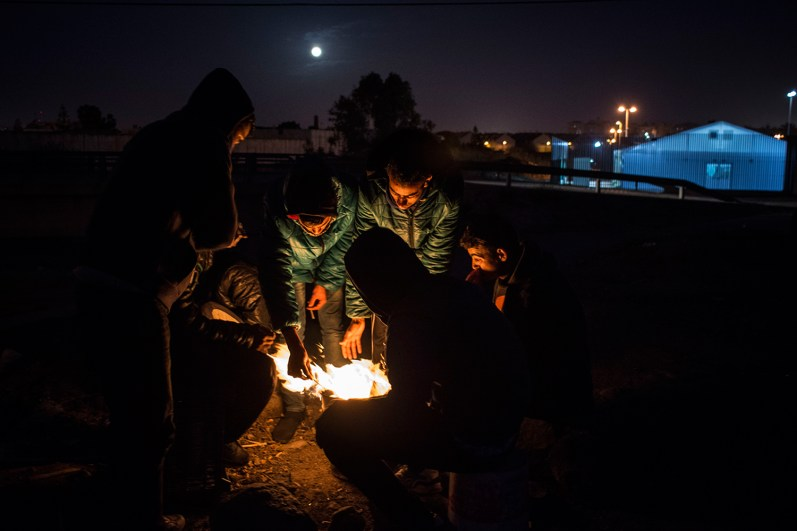 As the night falls, a group on men warm themselves near a fire in the old camp. A lot of people pass by, searching for warmth and companionship. Talking is the only way they have to pass the time, and as the fire burns, stories are shared and cigarettes are smoked.