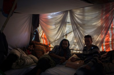 """Abdellatif (37) (center), chat with a friend from the CETI who is visiting. Badir (20) (left), listens to some music with his smartphone. He often manages to charge his phone inside the CETI. Abdelatif reached Spain on a boat 15 years ago, and found work in a small town near Madrid. A year ago he was forced to report his employer to the Ministry of Labor because he was not being payed. The result, he says, was an expulsion order. He has spent the last year trying to get his old life back. """"This is the house of the people,"""" he jokes often, """"here all who do not have a place are welcome."""""""