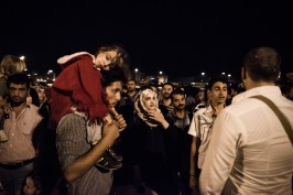 Refugees and migrants wait for buses after disembarking from the 'Tera Jet' highspeed ferry boat in the port of Piraeus, on September 1, 2015. Ferries from the islands continually bring more migrants and refugees to the port of Piraeus in Athens.