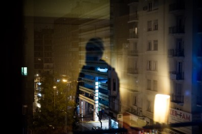 A reflection in windown of Abdala Omar Yahya, a refugee from Syria currently living in a hotel room in central Athens. Abdala fled Syria towards Turkey and in late December 2014 he crossed the Aegean Sea by boat to arrive in Greece in order to continue his journey to western Europe.