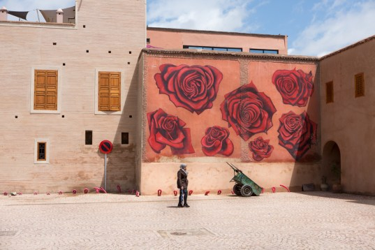 A woman walking the central streets of Marrakech. Behind her, a graffi: of red roses painted on an old building.