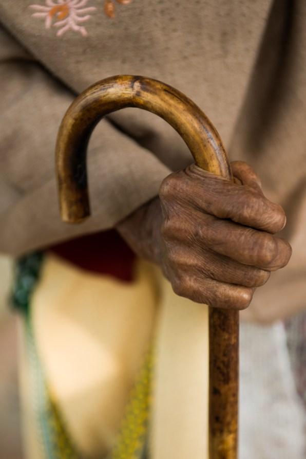 Close-up of Kiran Dasi's hand and walking stick.