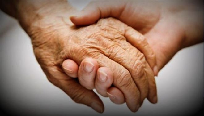 elderly holding hands with young person