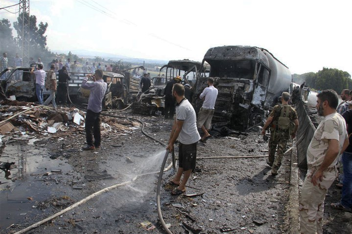Mideast Syria-1 Syrian security forces, emergency services and residents look at the remains of burned vehicles at the site of a bombing in Tartus on Sept. 5.