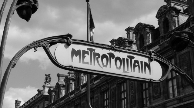 "Black and white photo of the Paris Metro's ""Metropolitain"" signs with French buildings in the background"