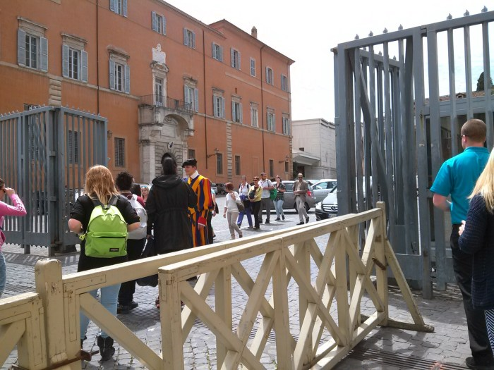 As you are facing the Basilica, the entrance to the Excavations office is to the left and behind the curved collonade. A Swiss guard will admit you.