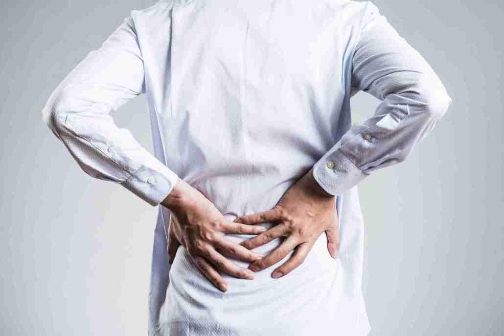 Uomo in camicia con mal di schiena - Foto per Testimonianze Video con Categoria Lombalgie