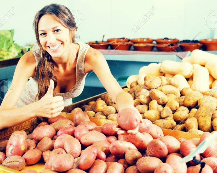 Portrait of young girl buying potatoes