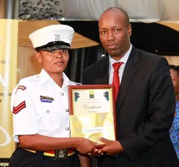 NTSA Boss Lee Kinyanjui hands over an awards to CPL Mwanahamisi Sheria from Nyeri traffic base during the AKI road Safety awards Ceremony