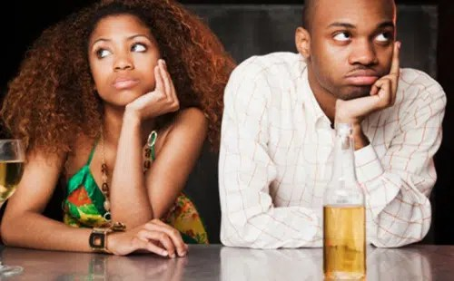 Couple sitting at bar and looking irritated. Image from http://thelibertarianrepublic.com/black-couple-pissed-after-seeing-black-couple-on-receipt-waitress-fired/