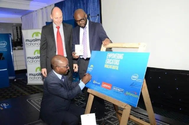 INTEL East Africa General Manager, Danie Steyn and Microsoft's General Manager for East Africa- Kunle Awosika look on as Mwalimu National Sacco CEO- Robert Shibutse signs the agreement. Image courtesy of Intel.