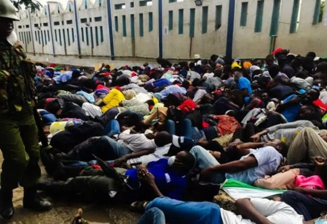 Kenyans lying on the ground as a police man looks on enforcing the Covid-19 curfew - Ministry of Health & Govt. Guidelines