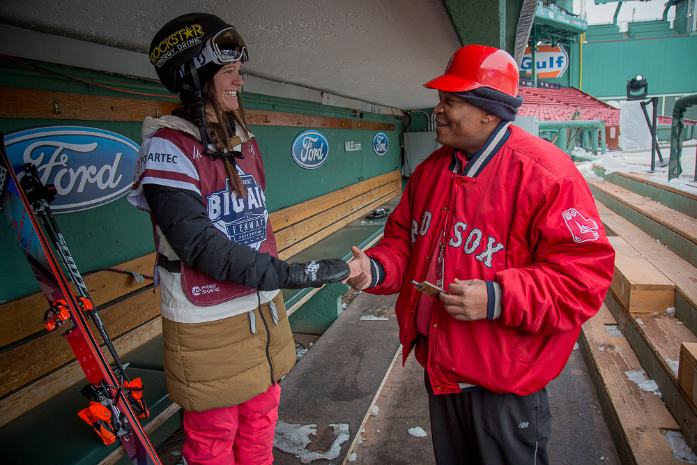 """Keri Herman chats it up with Mario Batista, a Fenway grounds crew member and new ski fan. Asked what he thinks of the massive scaffolding structure sitting in the middle of his ballpark, Batista responds, """"It's just crazy, man. I mean, it's cool, but these guys…they're crazy."""" PHOTO: Kade Krichko"""