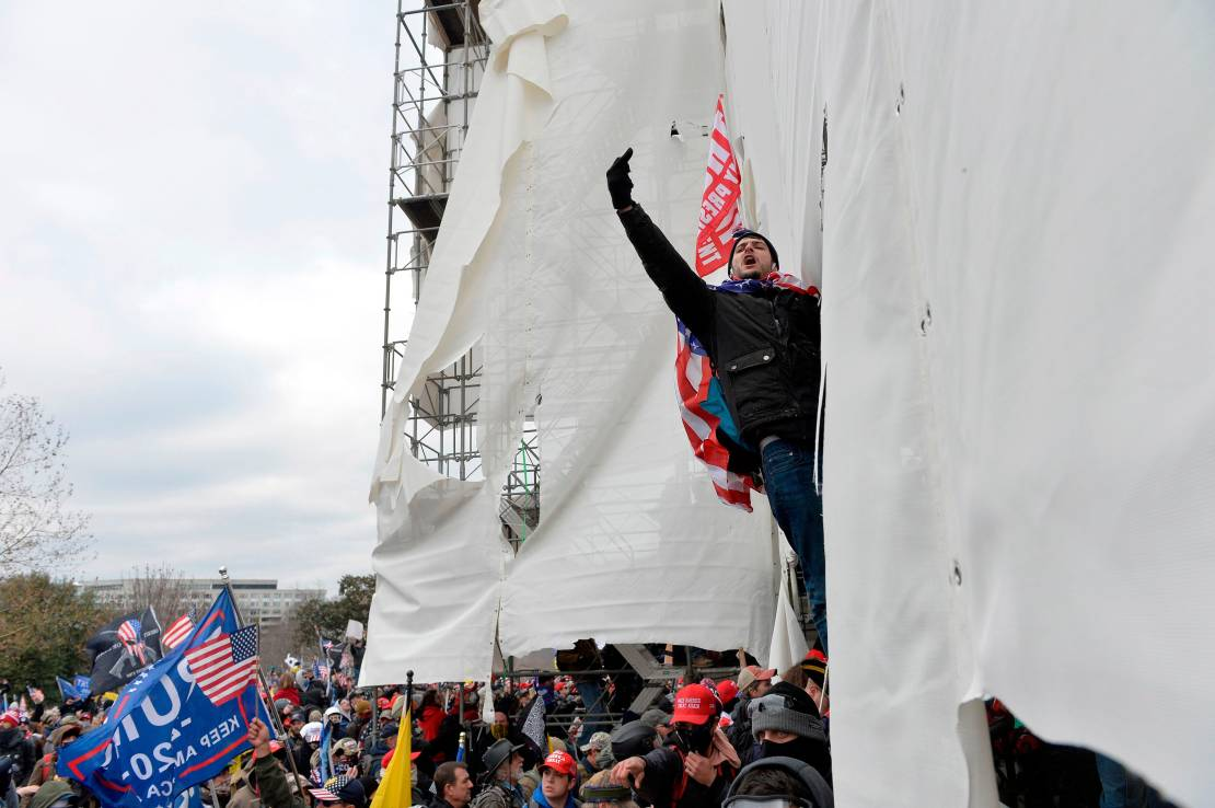 Rioters clash with police and security forces, climbing scaffolding as they try to storm the US Capitol.