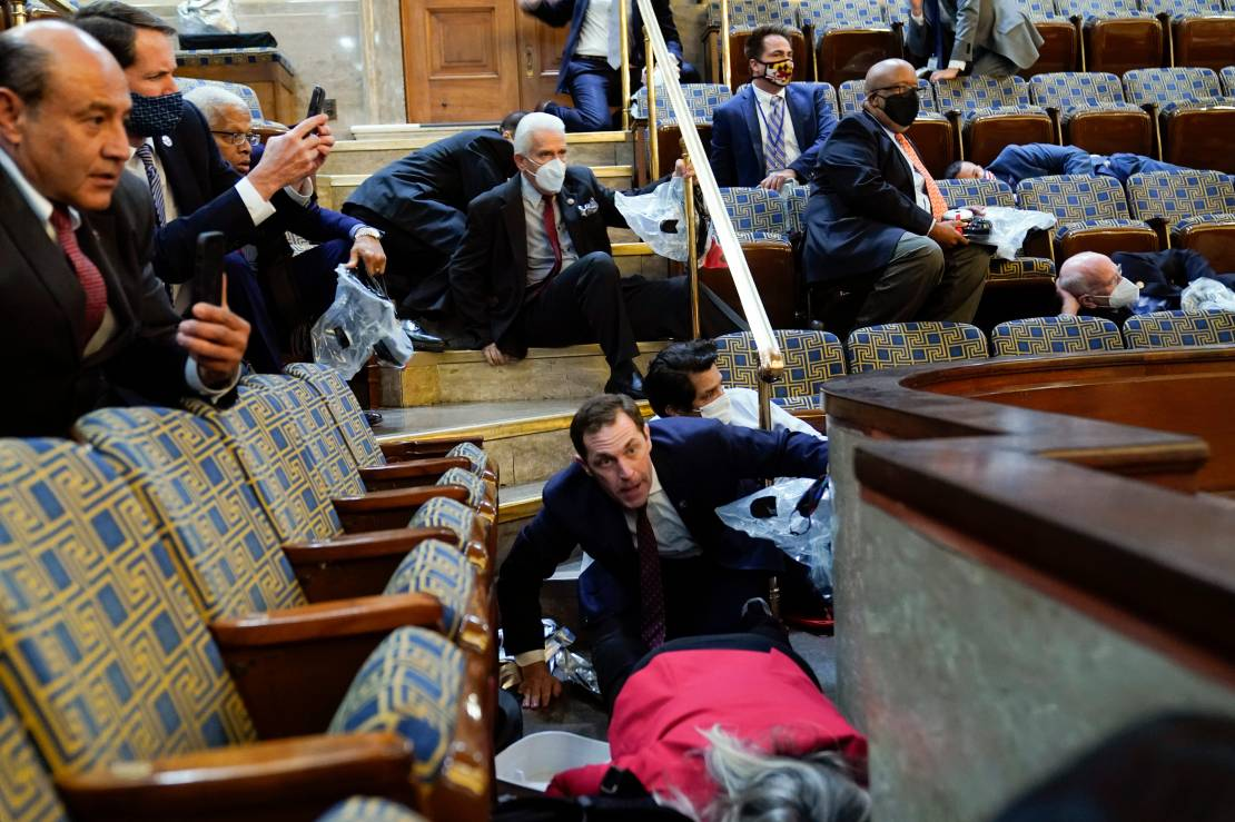People shelter in the House gallery as rioters try to break into the House Chamber at the U.S. Capitol.
