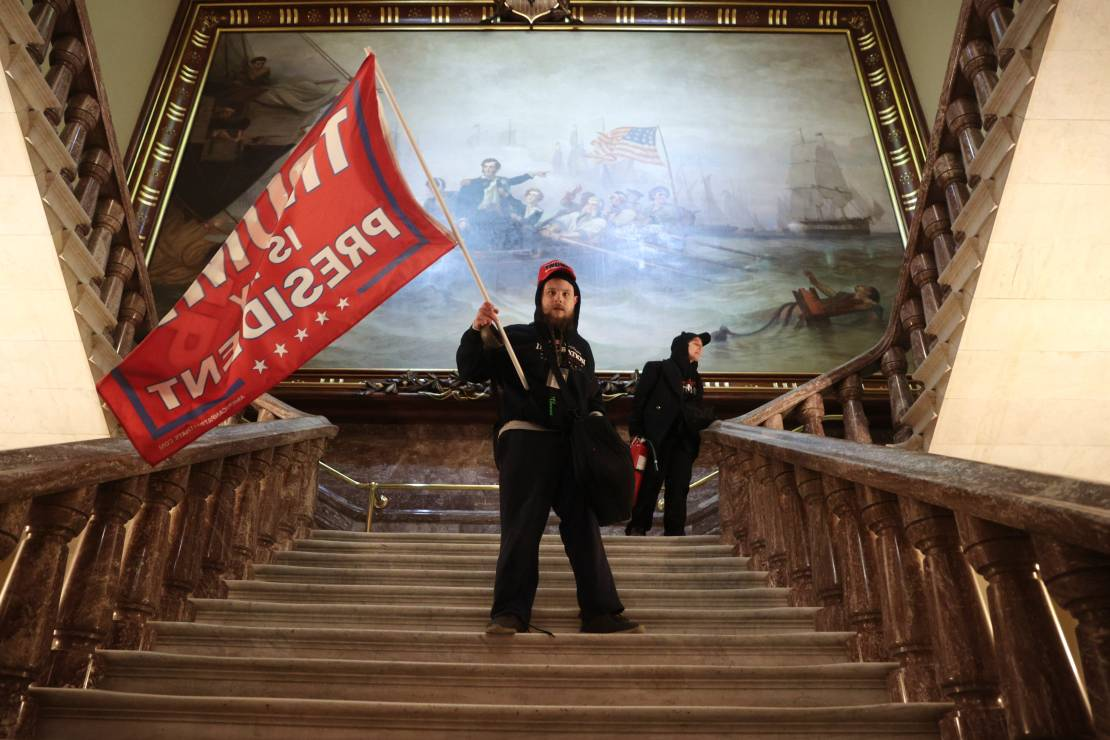 A rioter holds a Trump flag inside the US Capitol Building near the Senate Chamber.