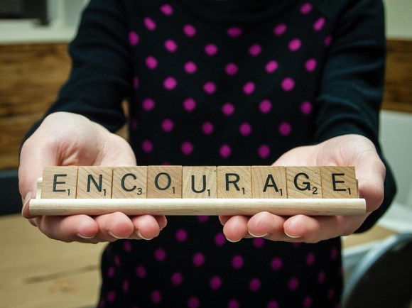 A woman holding a scroll with a written word 'Encourage'