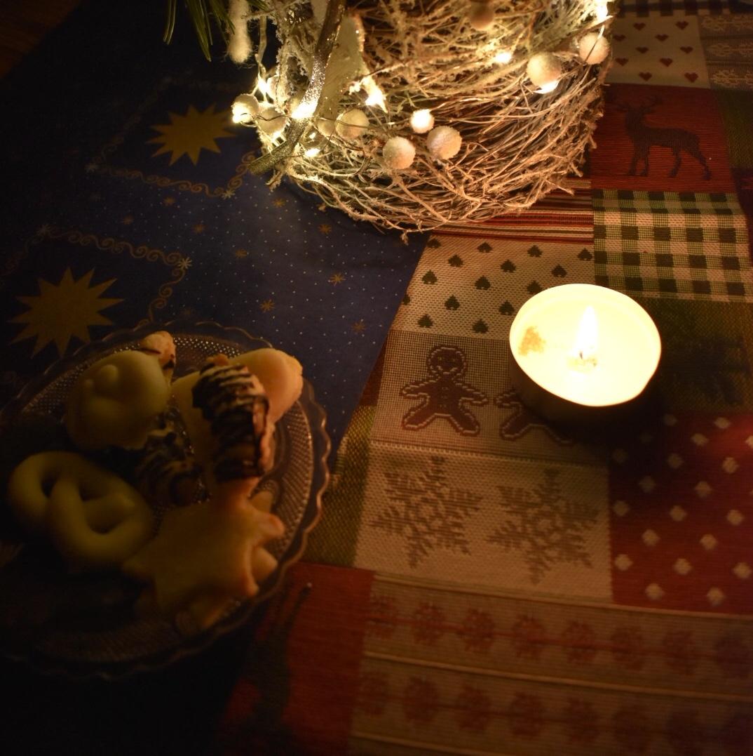 Weihnachtliches Stillleben im Kerzenlicht mit Plätzchen und weihnachtlicher Tischdekoration