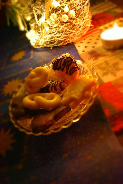Weihnachtsplätzchen auf einem Glasteller im Kerzenlicht