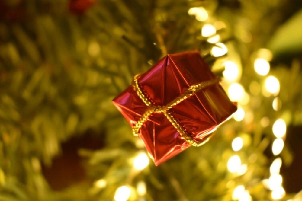 Rotes Geschenkpäckchen vor einer Lichterkette