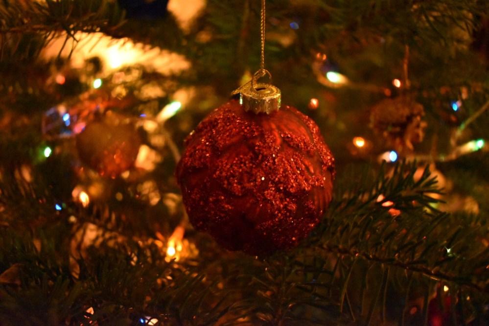 Rote Kugel in goldenem Licht an einem Tannenbaum hängend