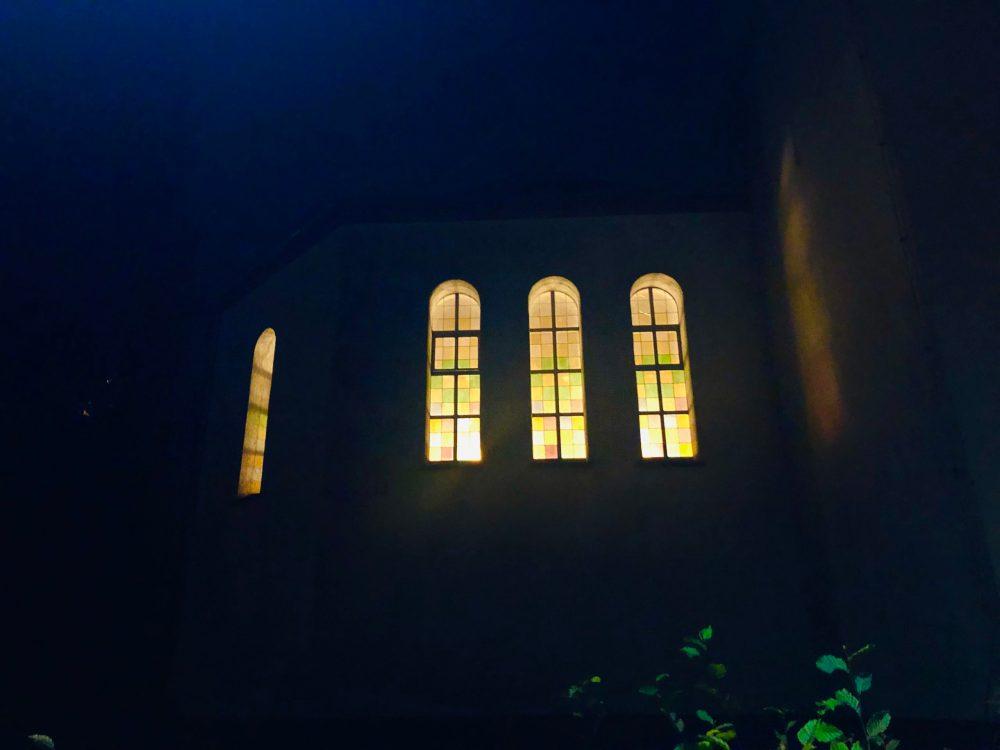 Kirche mit leuchtenden Fenstern im Dunklen