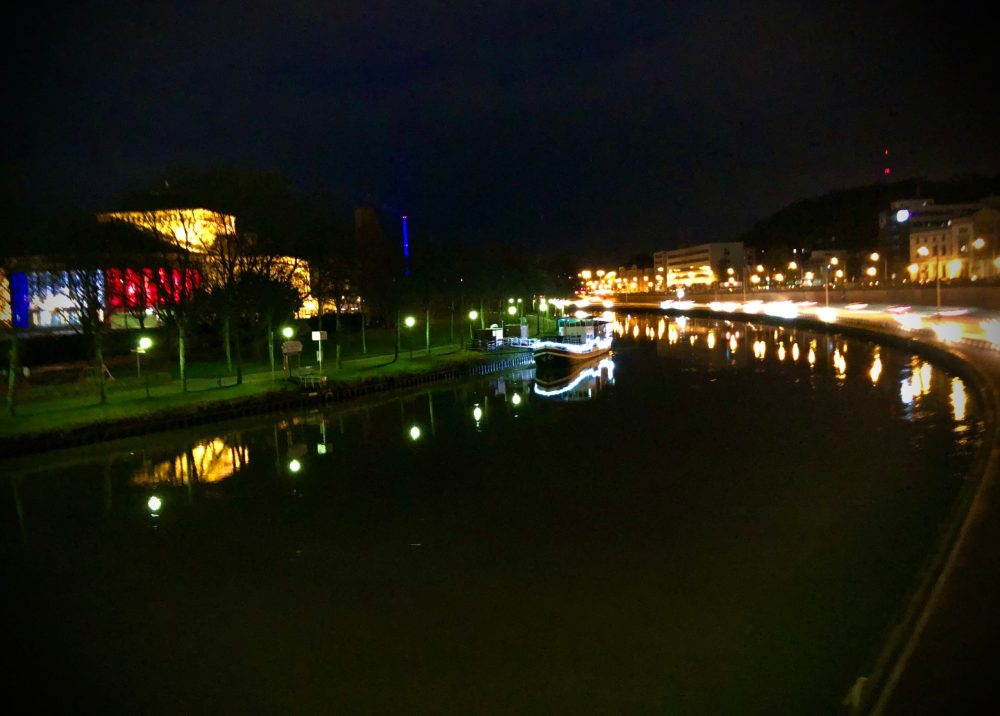 Beleuchtetes Schiff auf der Saar neben dem Staatstheater im dunklen