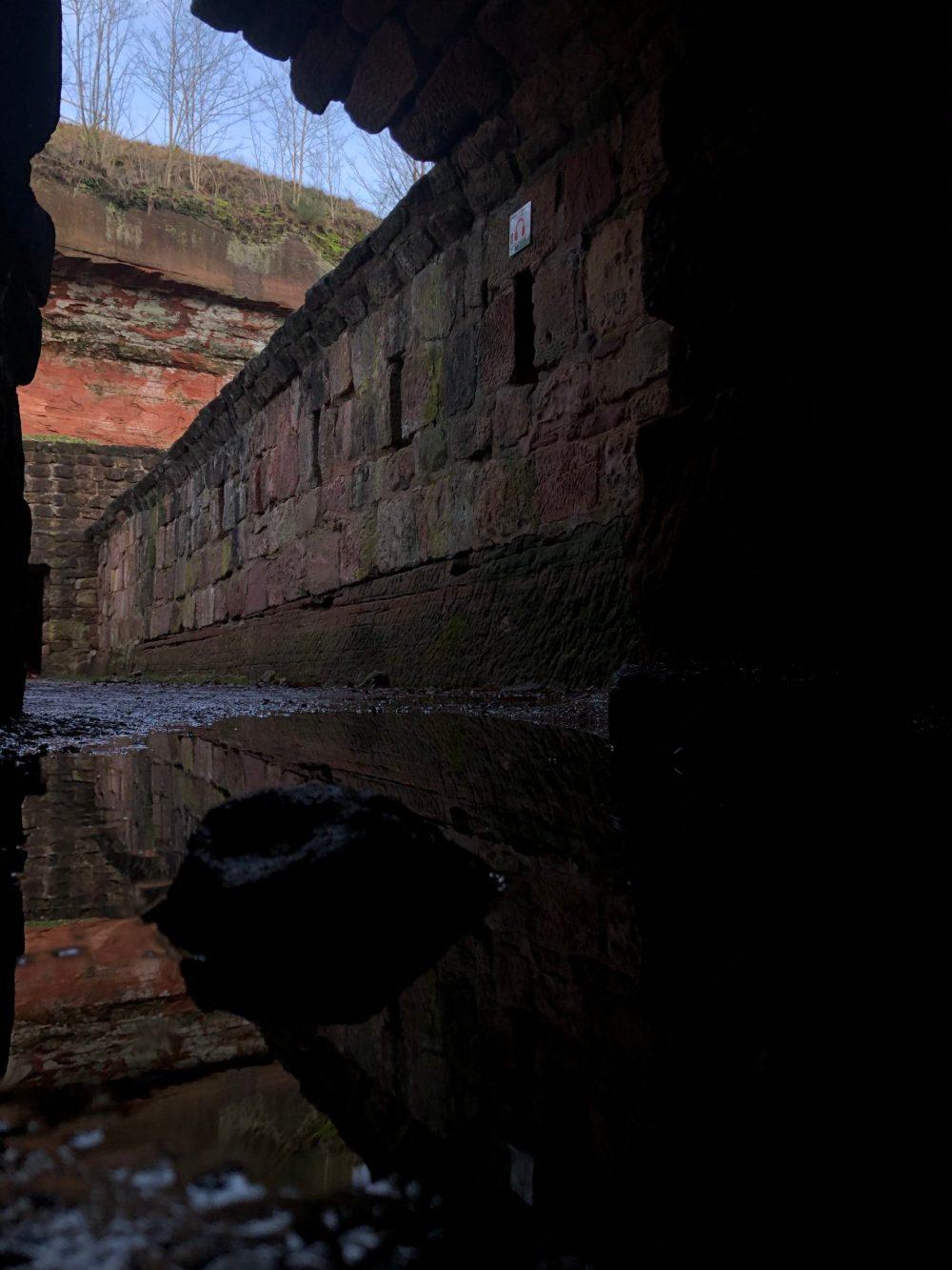 Pfützen Fotografie  vor einem alten Durchgang mit Schießscharten